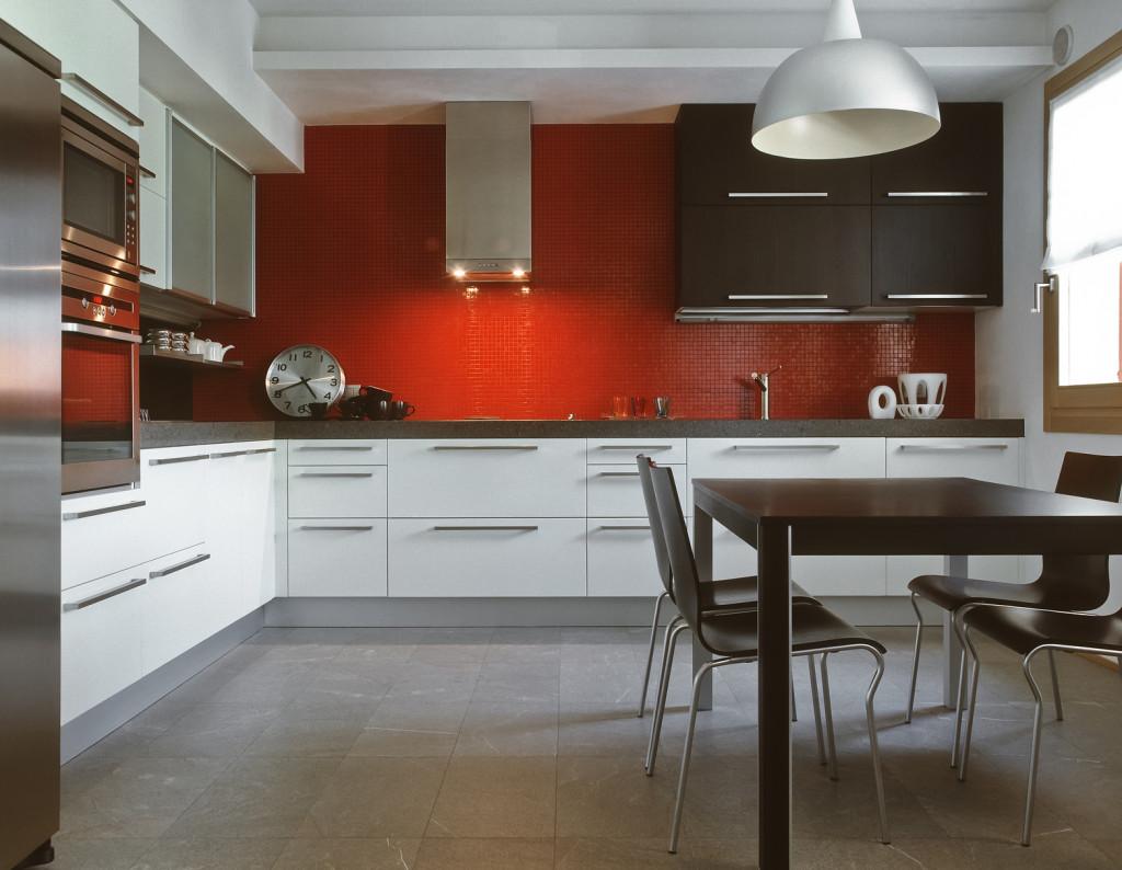Moderní hnědobílá kuchyně s červeným obkladem.