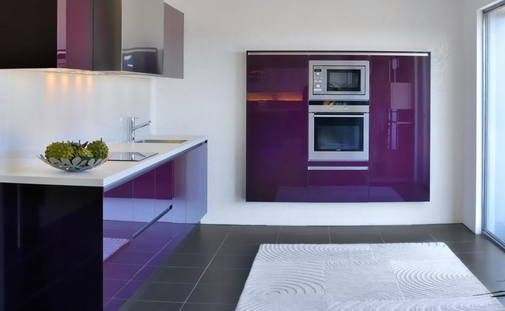 Moderní kuchyně ve fialovém lesku s bílou pracovní deskou.