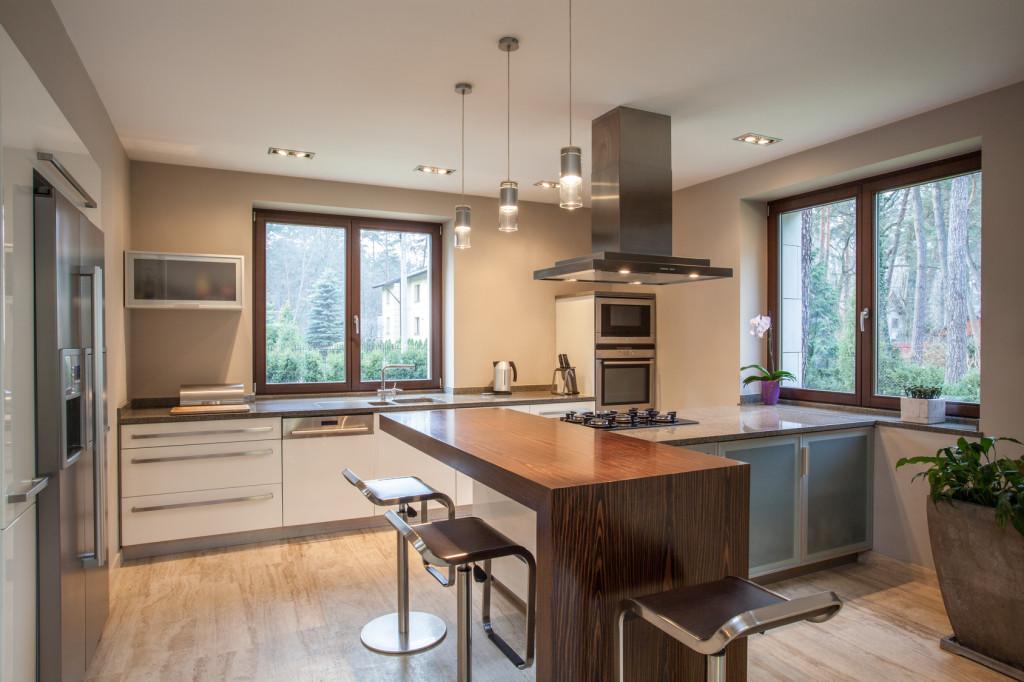 Světlá moderní kuchyně s dřevěným pultem.