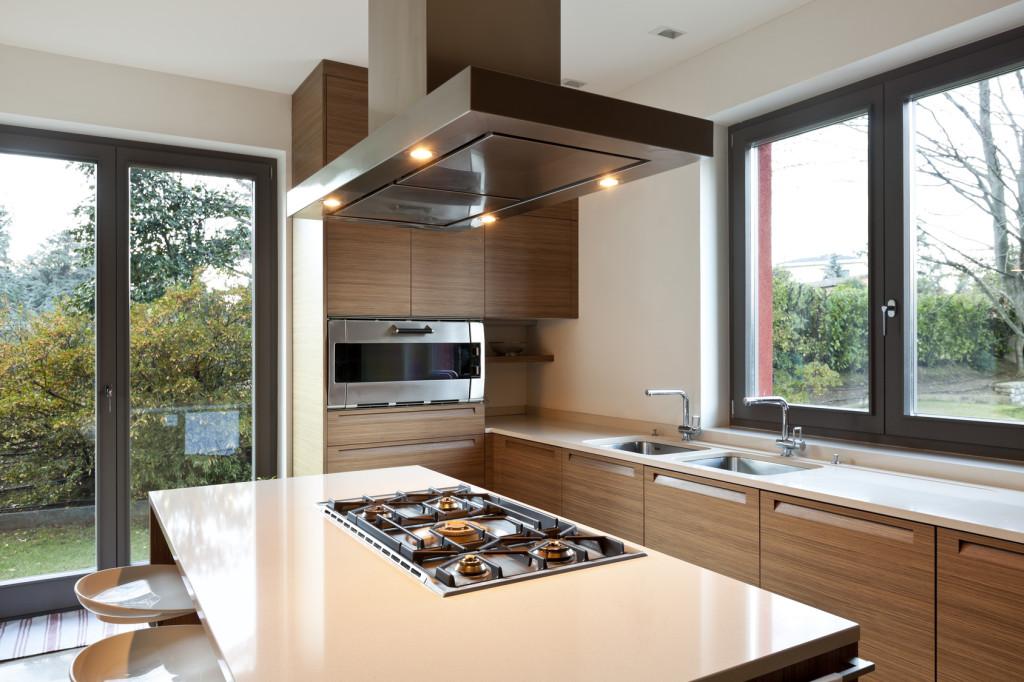 Moderní kuchyně s dřevěným dekorem a kuchyňským pultem.