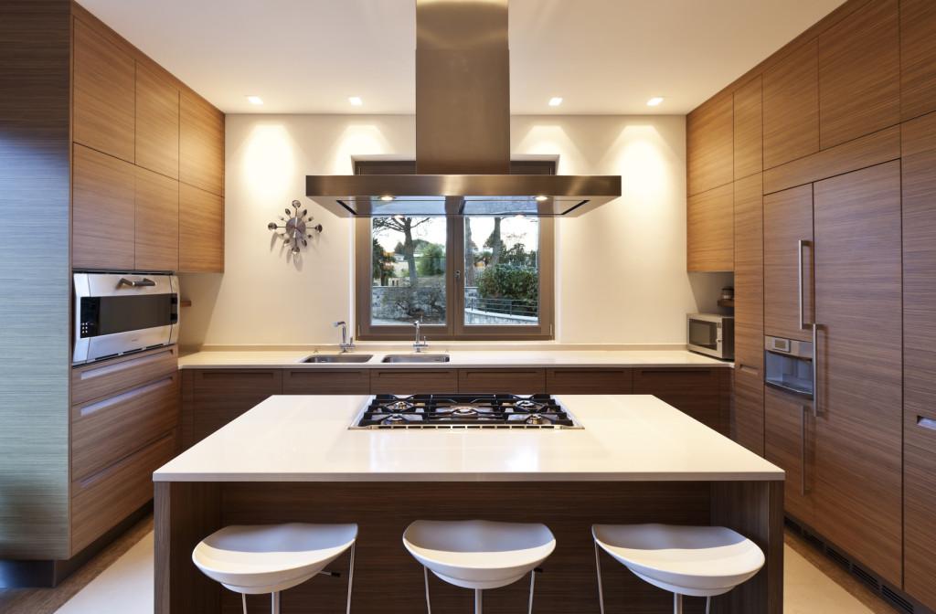 Moderní kuchyně se středovým pultem a dřevěným dekorem.