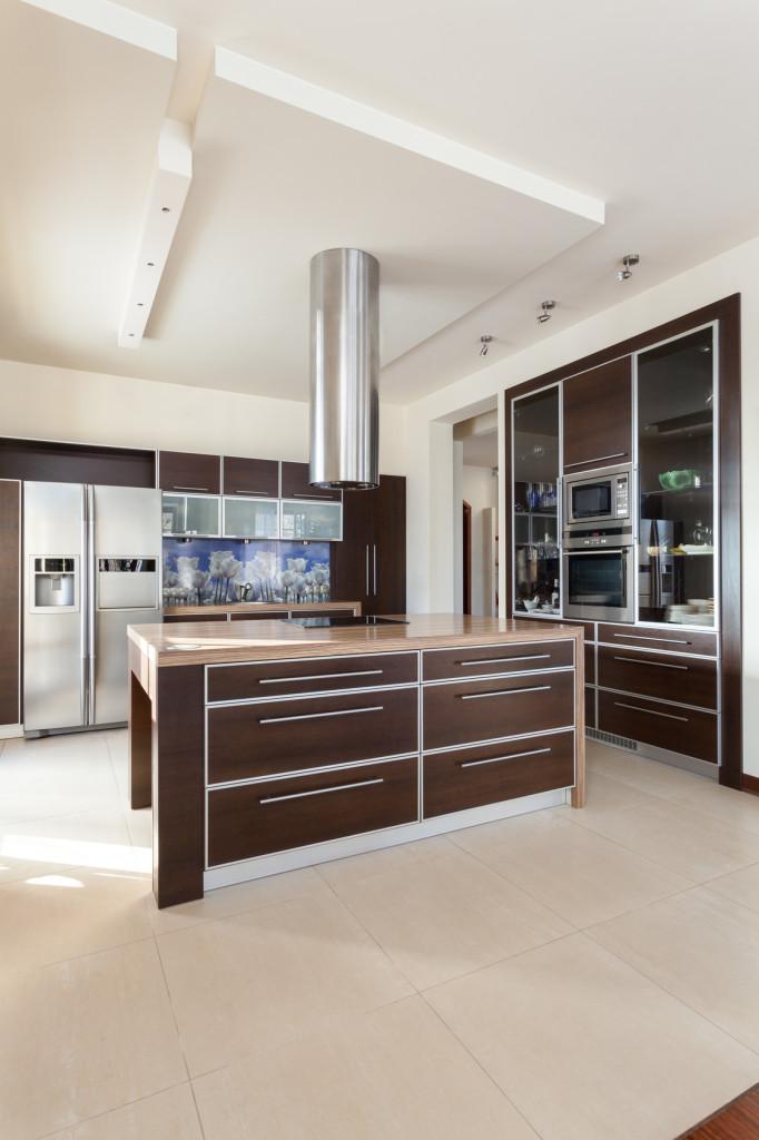 Moderní kuchyně se středovým pultem a s dekorem z tmavého dřeva.