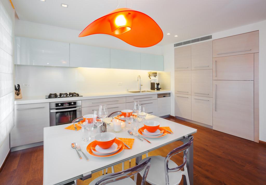 Moderní kuchyňský kout v bílé barvě s oranžovými doplňky.