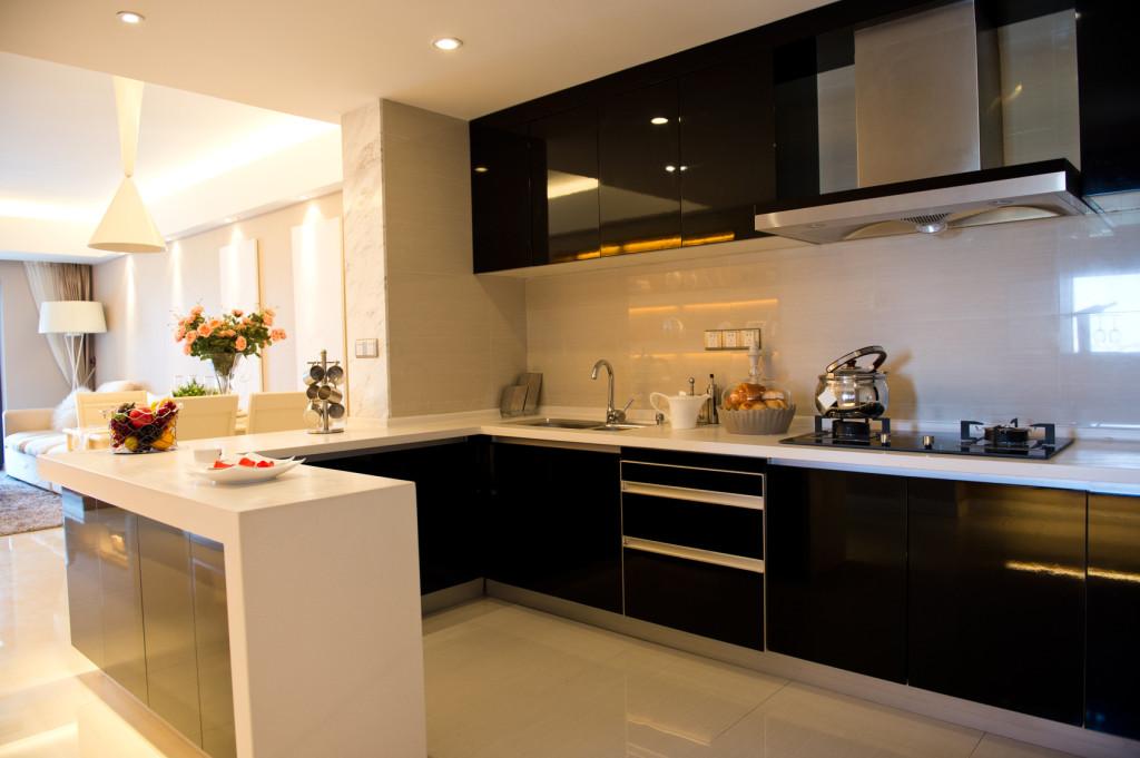 Moderní kuchyně v černé barvě s bílou pracovní deskou.