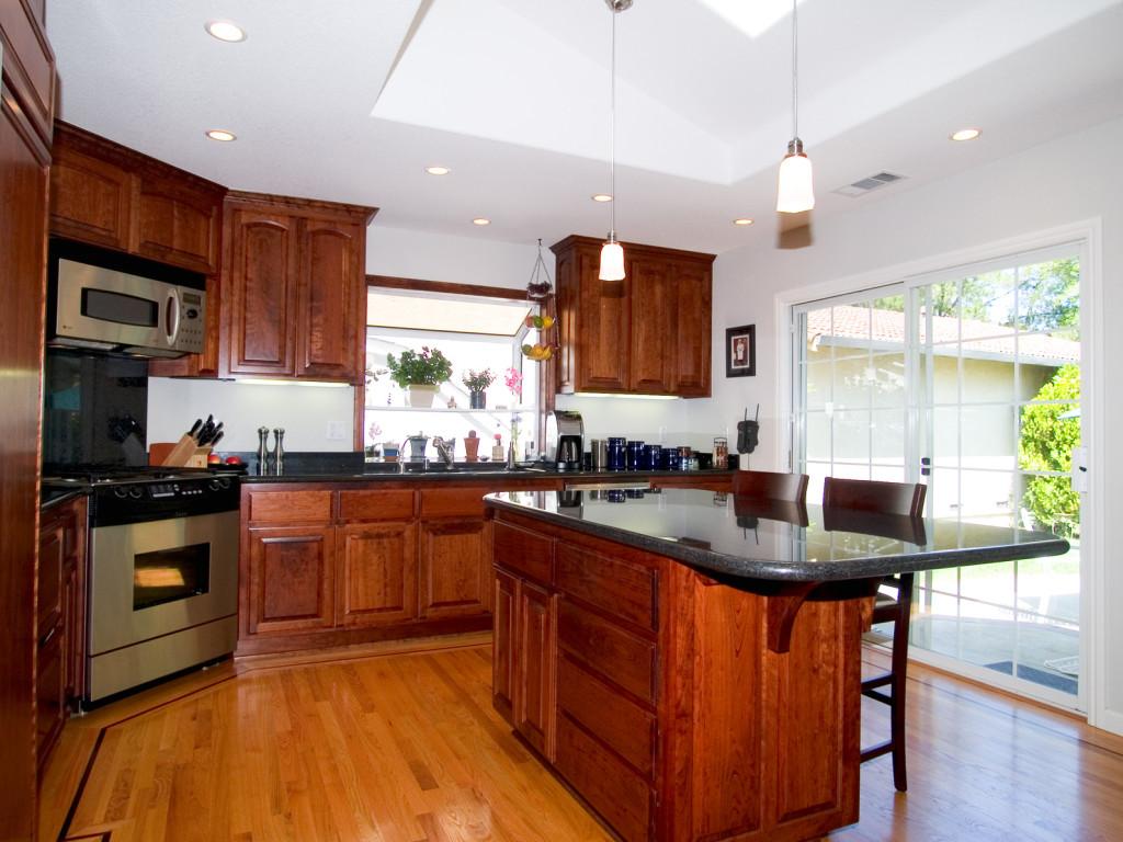Rustikální kuchyně v kombinaci tmavého dřeva a přírodního kamene.